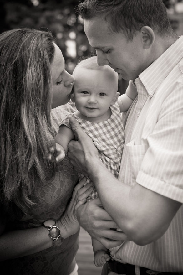 family mom and dad kissing baby