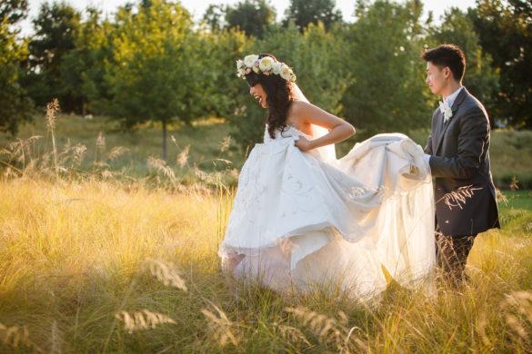 bride and groom walking through tall grass