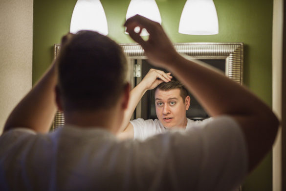 groom fixing hair in mirror