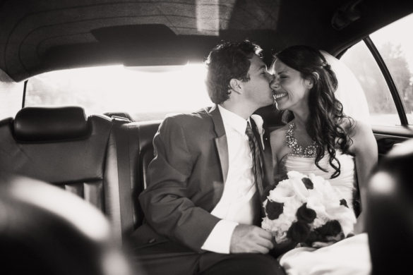 bride and groom kiss in getaway car
