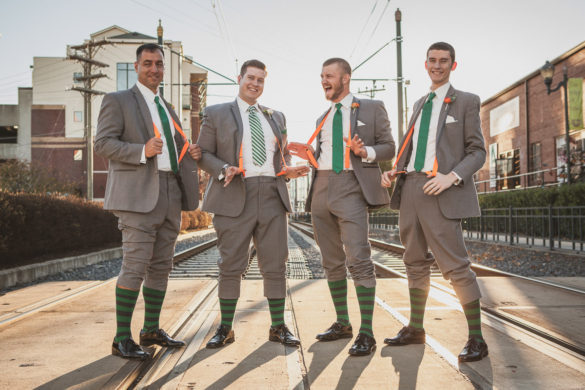 silly groomsmen pose train tracks
