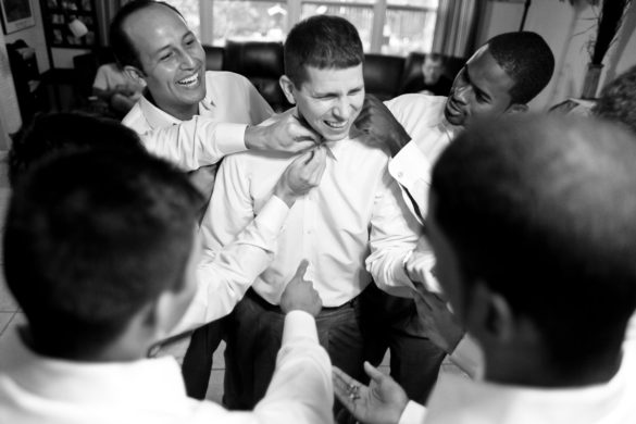 groomsmen helping groom get dressed