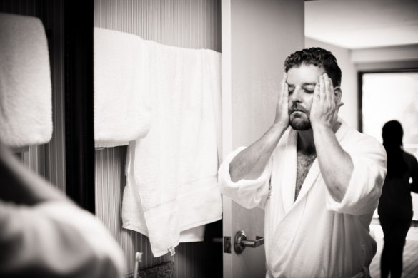 groom holding face in bathroom stress