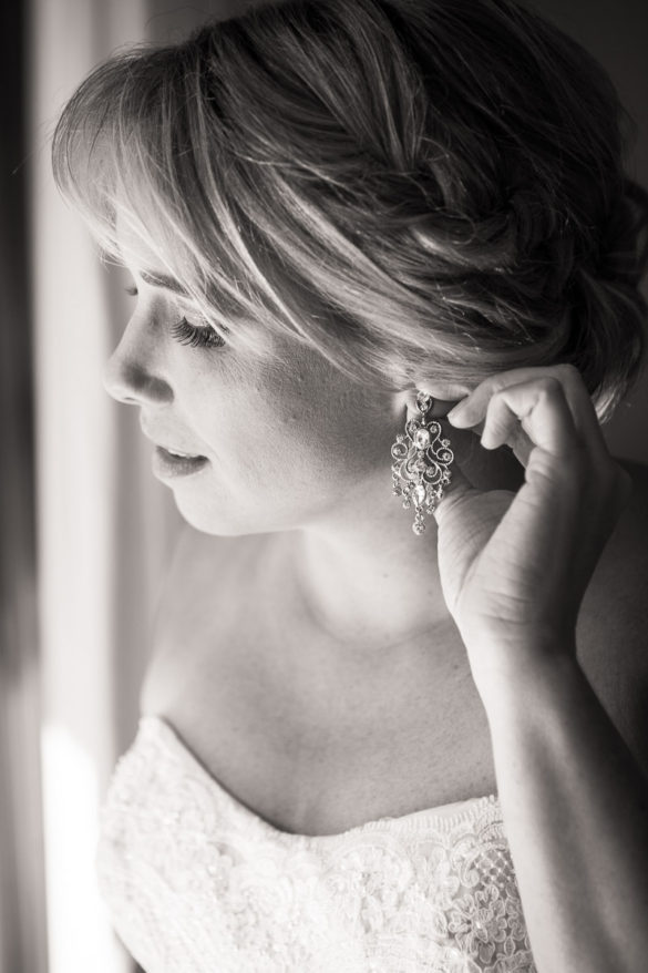 bride adjusting diamond earrings