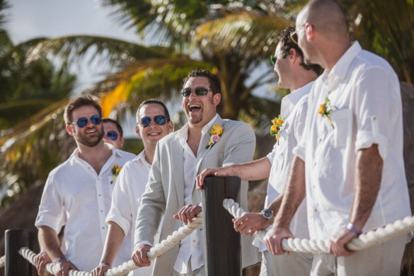 groomsmen laughing at the beach