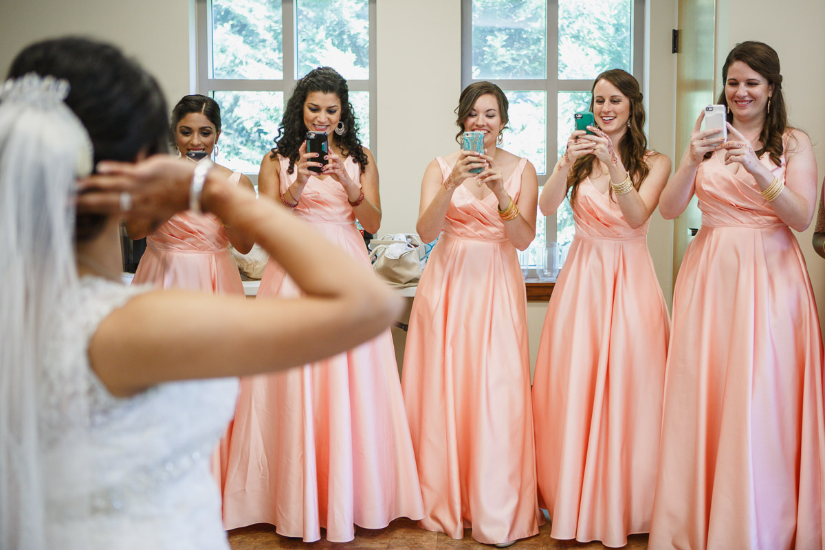 bridesmaids taking picture of bride